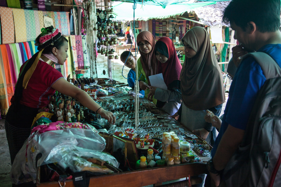 Tourists from Malaysia browse handicrafts at one of the many stalls lining the one main road through Huai Sua Tao.