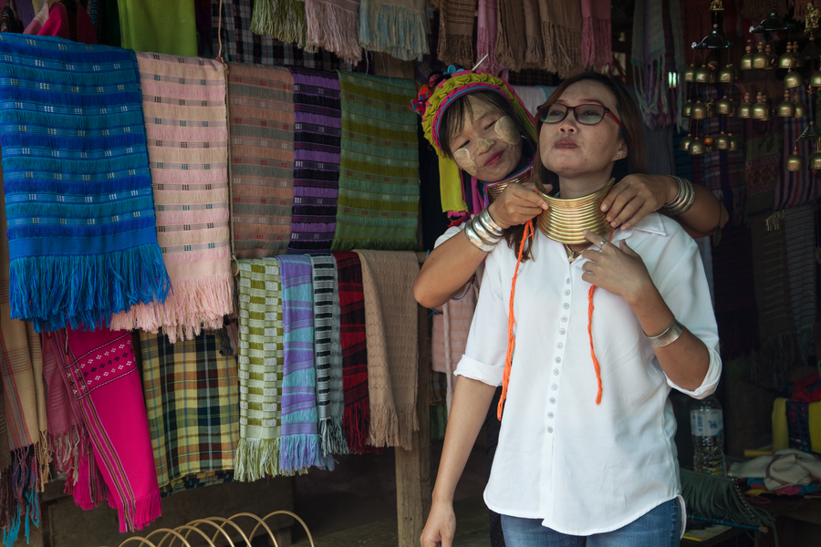 A Thai tourist tries on the brass rings that the Kayah women of Huai Sua Tao traditionally wear starting in childhood.