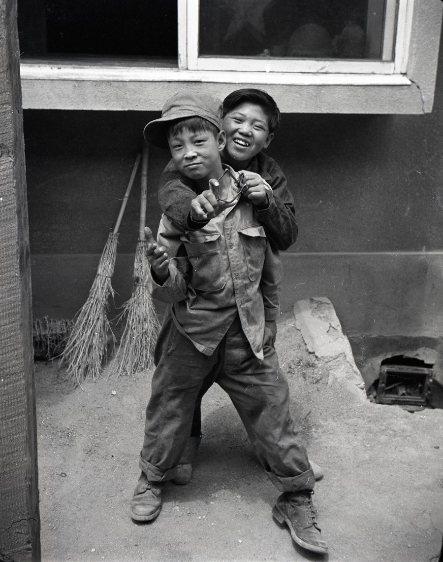 Two young houseboys pose for the camera during the Korean War.