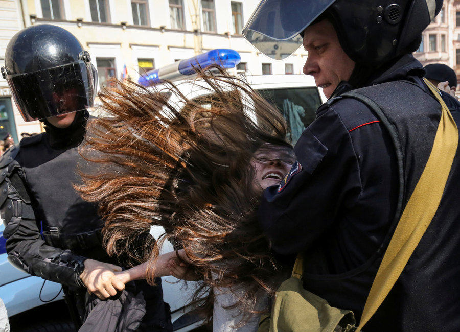 Two Russian police officers are shown with helmets and dark visors holding a woman who is resisting.