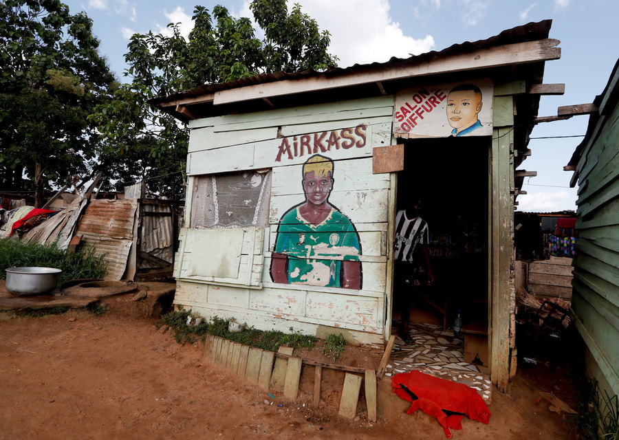 A small wooden building is shown with a painting of a soccer player on the wall.