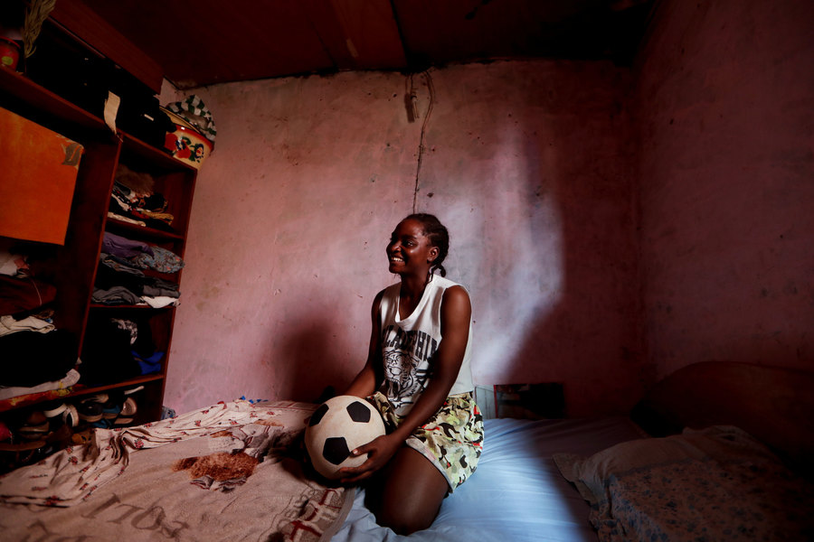 A young woman is shown sitting on her bed holding a soccer ball.