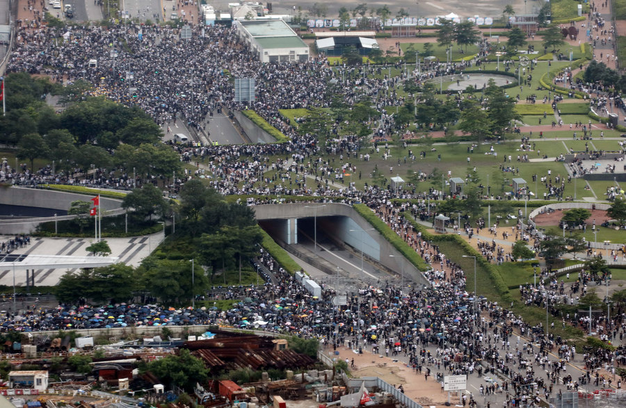Thousands of demonstrators are shown crowding a main road in Hong Kong in a photo taking from several stories up through a window.