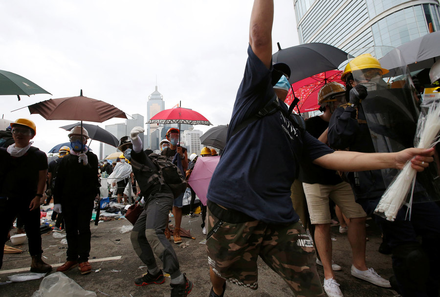 Several potesters are shown wearing masks and holding umbrellas with one person center frame who is about to throw and object.