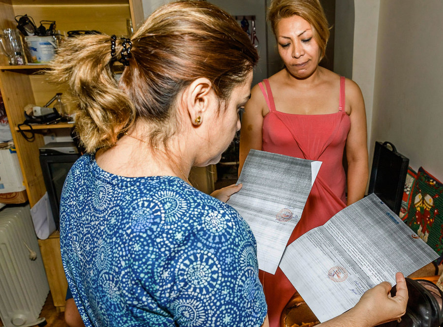 A woman is shown in the nearground holding two pieces of official documentation with another woman in a dress standing in the background.