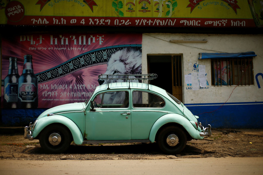 A greenish-blue colored Volkswagen Beetle is shown with a metal rack on top and parked in front of a store.