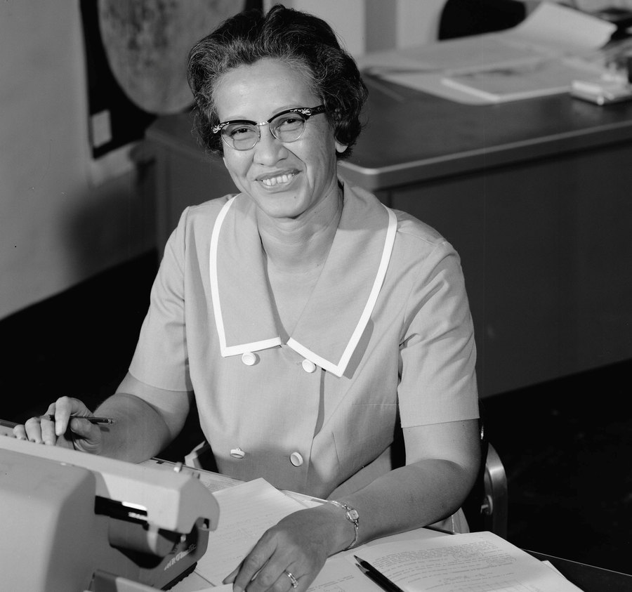 NASA research mathematician Katherine Johnson is shown in a portrait photo sitting at a desk with a typewriter on it.