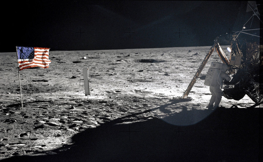 A US flag is shown on the moon adjacent to the Lunar Module.