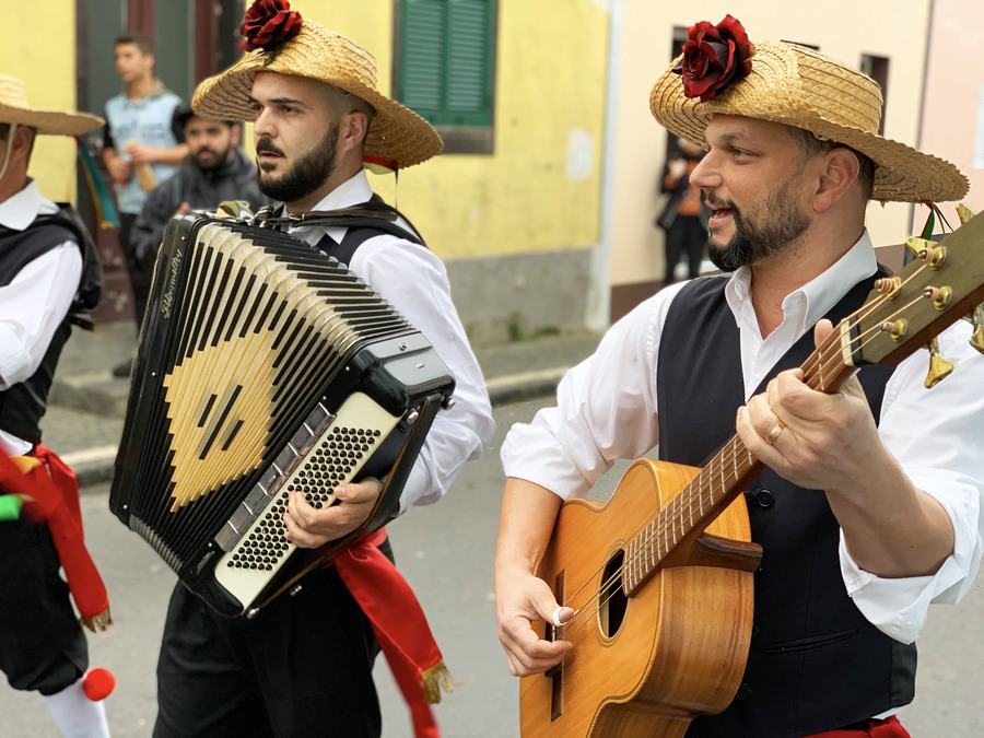 Musicians walk down the street in hats. One plays a guitar, one an accordion.