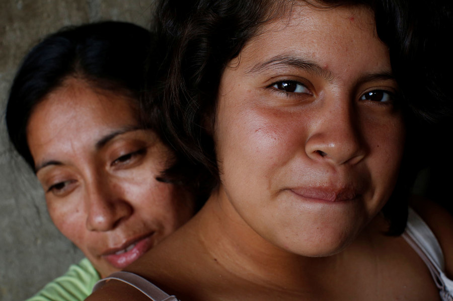 An older woman and her teenage daugter show shown in a close-up photograph with the daughter looking directly at the camera.