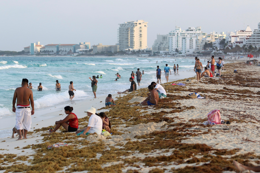 Tourists are seen on a beach covered with seaweed in Cancun.