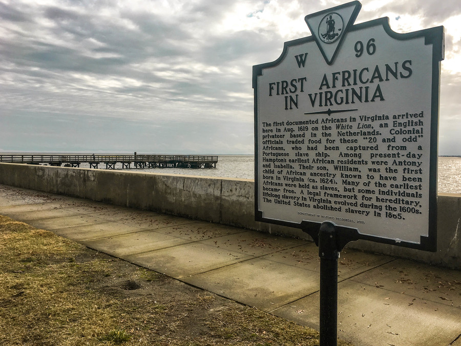 A sign marking the arrival of the first enslaved Africans in front of a seascape.