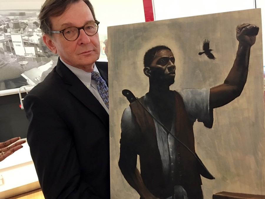 A white man in glasses and a suit holds a painting of a black man with a raised fist wearing a shirt and vest.
