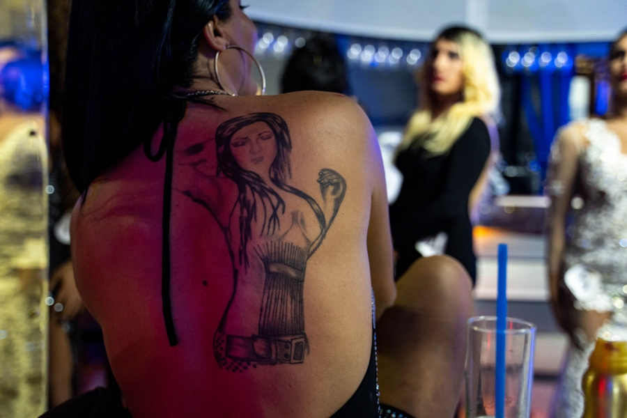 A tatoo is shown on the back of a person in dark outline showing a woman with long hair and her arm raised.