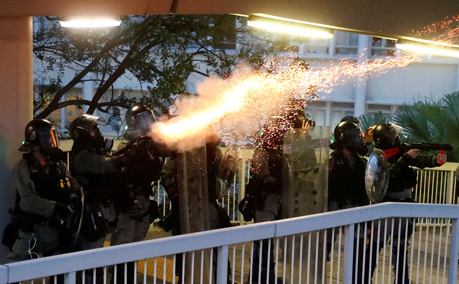 Police officers fire tear gas at demonstrators during a protest in Hong Kong