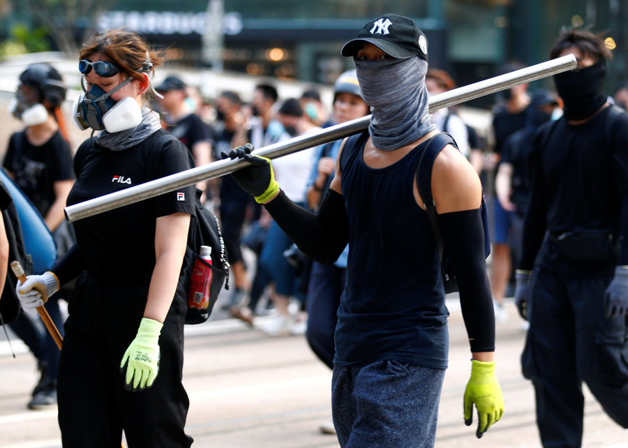 A protester carries an iron bar outside Causeway Bay station in Hong Kong