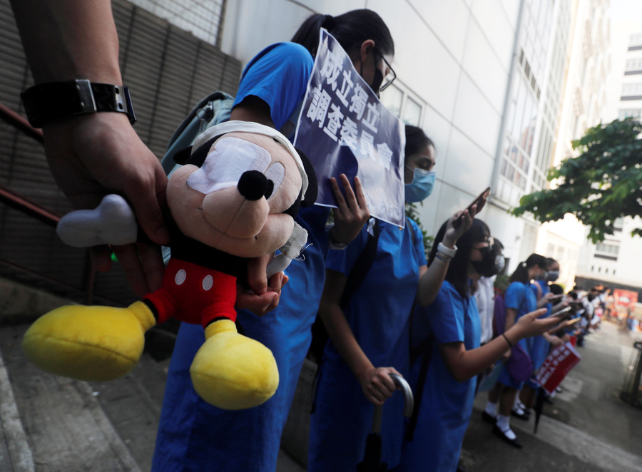 Secondary school students hold a Mickey Mouse stuffed doll with an eye patch as they form a human chain