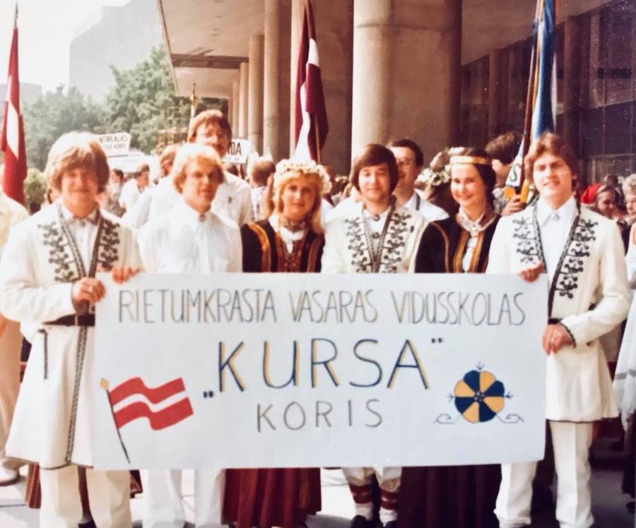 An archival photo of teenagers in folk costumes holding a sign