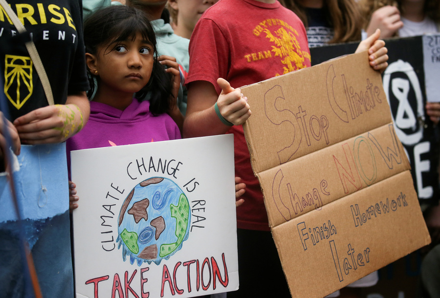 "A young girl holds a sign reading ""climate change is real, take action"" among other young protesters."