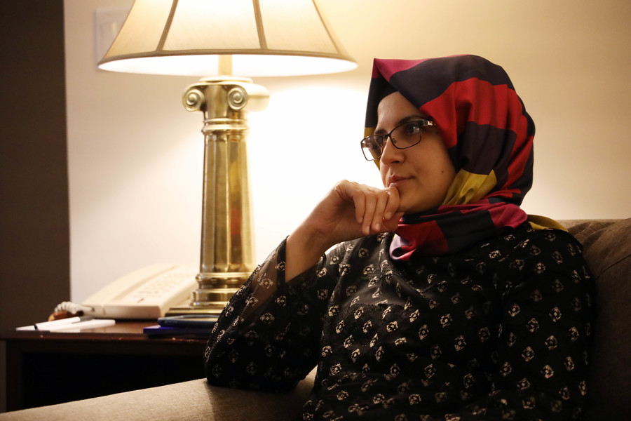 A woman in a headscarf sits on a couch