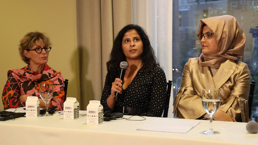 Three women sit on a panel in a conference room