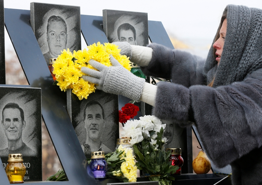 A woman lays flowers during a commemoration ceremony in front of a monument with images of men