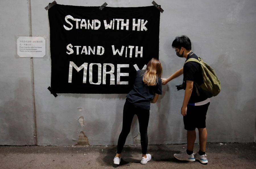 "A young woman and a young man hang a banner reading ""Stand with HK/Stand with Morey"""