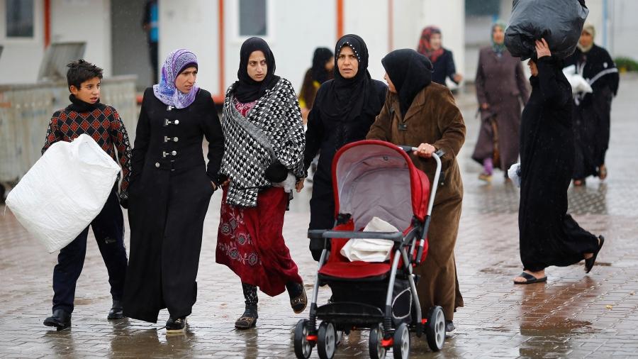 Syrianrefugee women walk and push a stroller