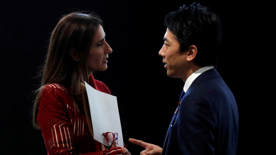 A woman speaks to a man against a black backdrop.