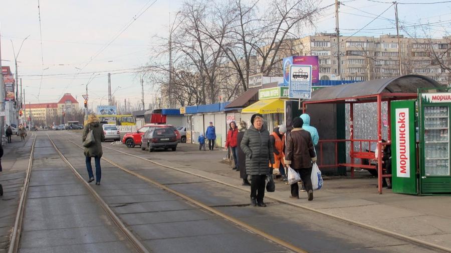 A tram line cuts through a suburban neighborhood in Kyiv, Ukraine, as people walk on the street.