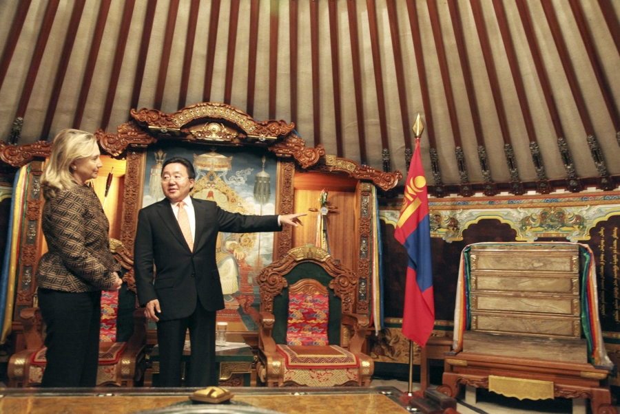 A man gestures toward a flag and ornate furnitures as a woman looks on.