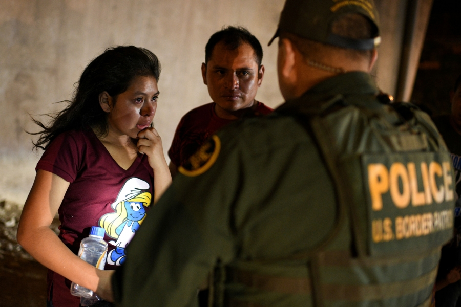 A young girl is shown standing in front of a Border Patrol officer and crying.