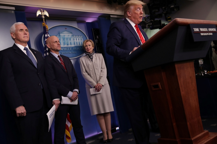 President Trump stands at a White House podium with officials behind him.