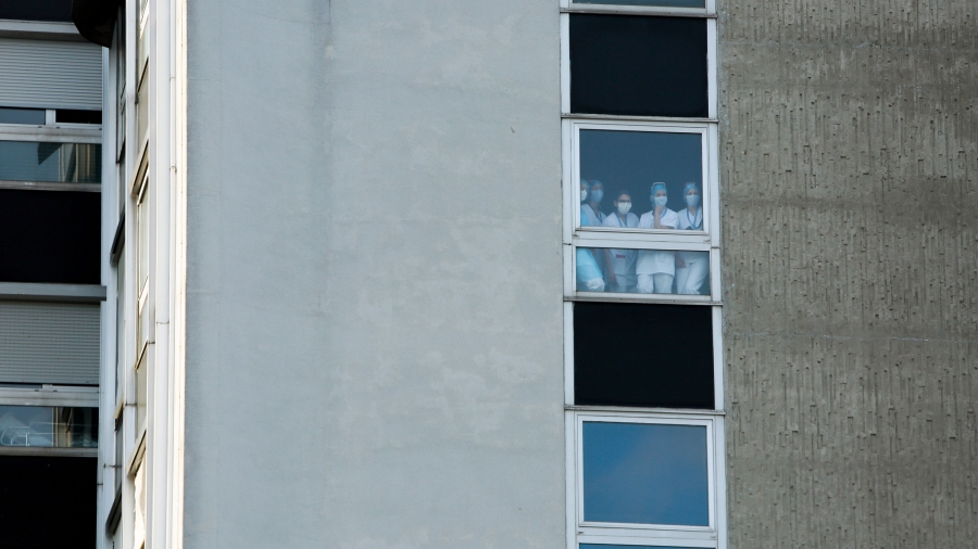 Medical personnel are shown standing in a window wearing protective medical gear and photographed from far outside of the building from below.
