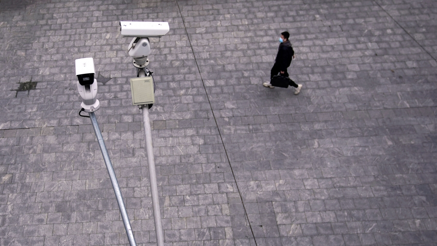 Two surveillance cameras are shown in the nearground with a man walking in a stone walkway and wearing a protective face mask in the distance.