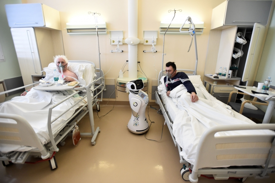 Two patients wear oxygen masks in a hospital and look at a small robot.