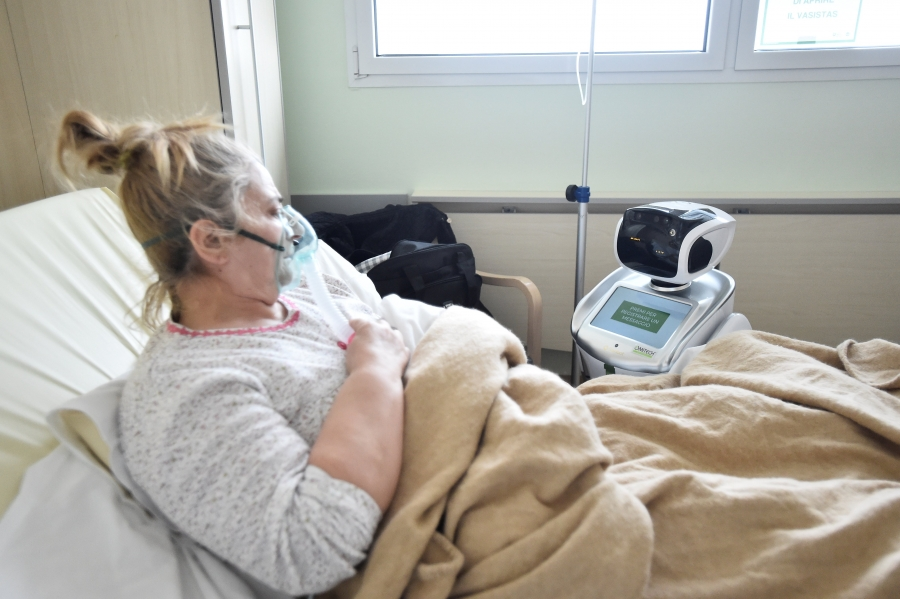 A sick woman looks at a robot from her hospital bed.