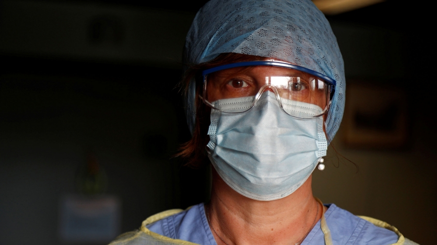 A close-up photograph of a doctor a wearing protective face mask and goggles.