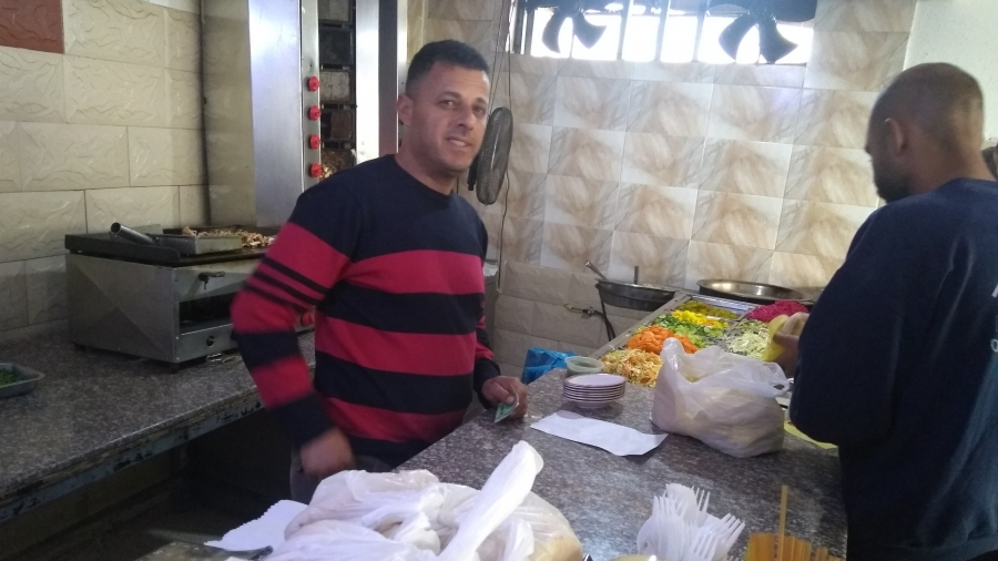 Two men stand at the counter preparing falafel at the Fence café in Baka al-Gharbiyeh.