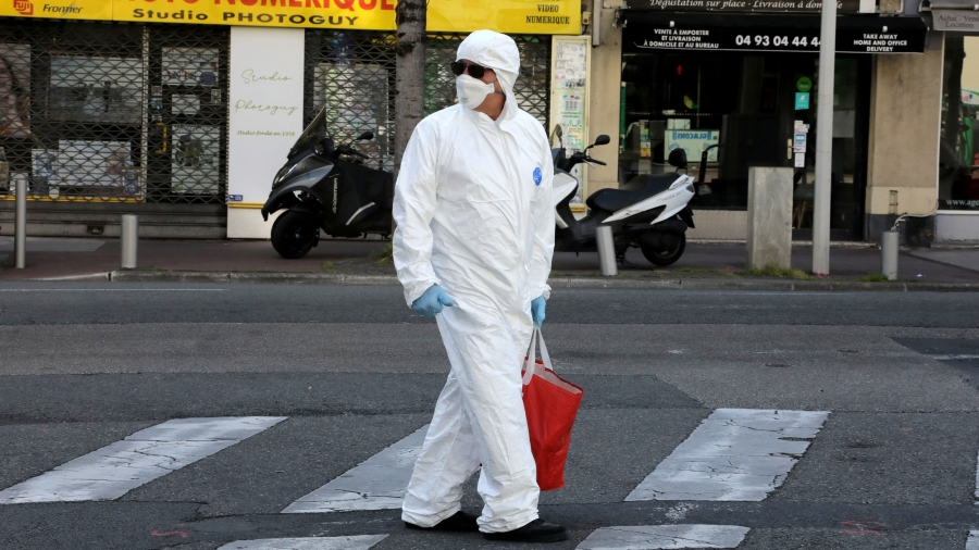 A man wearing a white protective suit and face mask with sunglasses is shown looking over his shoulder while walking in a street.