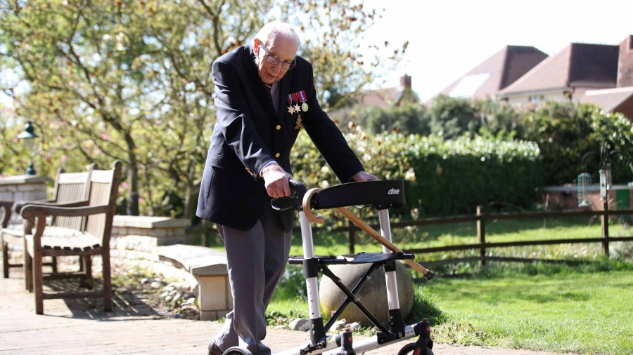 Retired British Army Captain Tom Moore, 99, walks to raise money for health workers, by attempting to walk the length of his garden one hundred times before his 100th birthday this month as the spread of coronavirus disease continues, April 15, 2020.