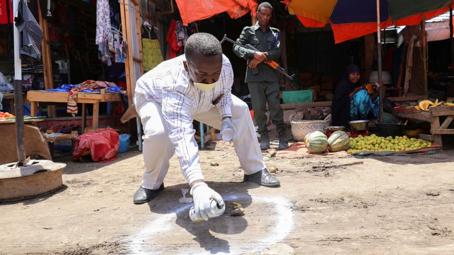 A man is shown bent over and spaying a white circle on the ground with a man nearby holding a weapon.