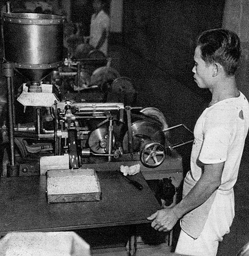 A man stands by a machine in this black and white photo