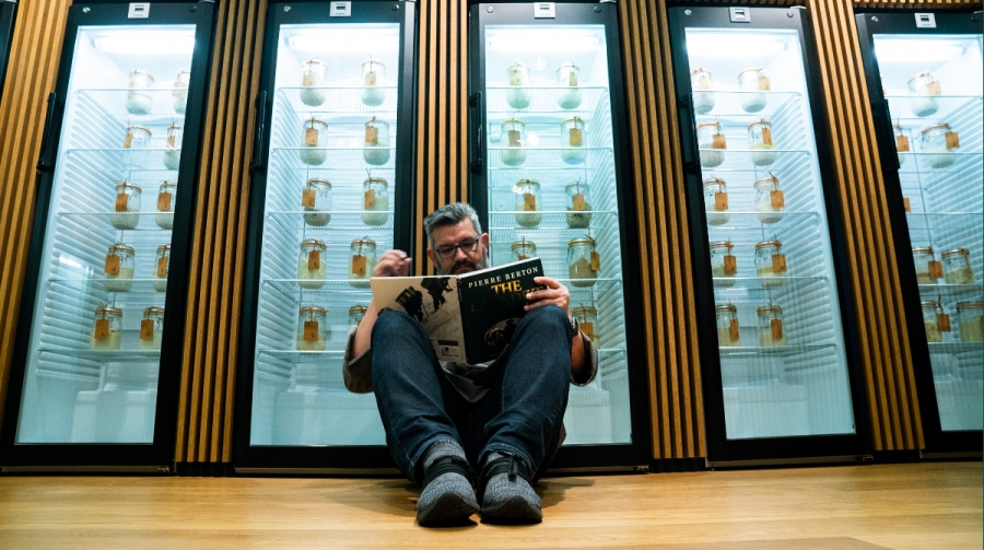 a man sits on the floor, reading a book in front of glass door refrigerators that contain jars.