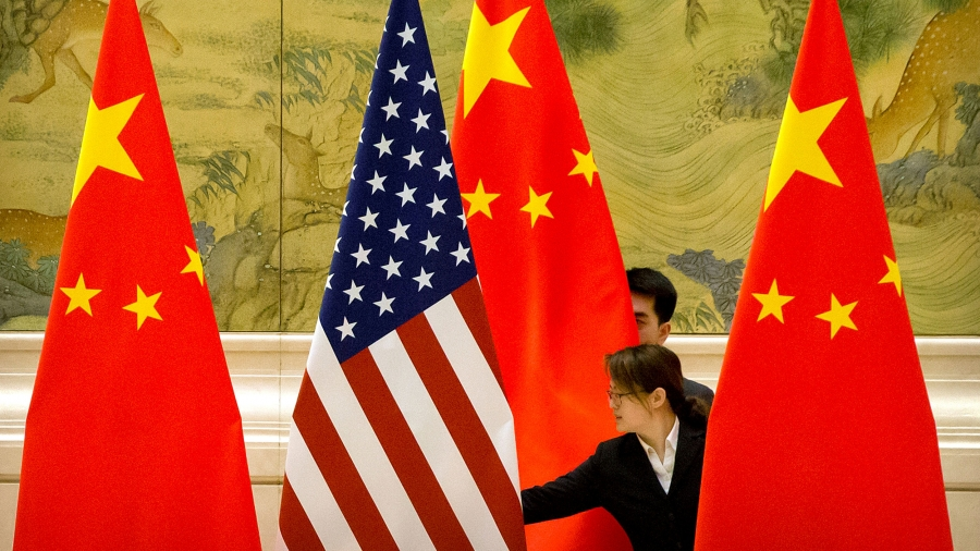 One US and three Chinese flags are shown being straightened by a woman standing in the middle of them.