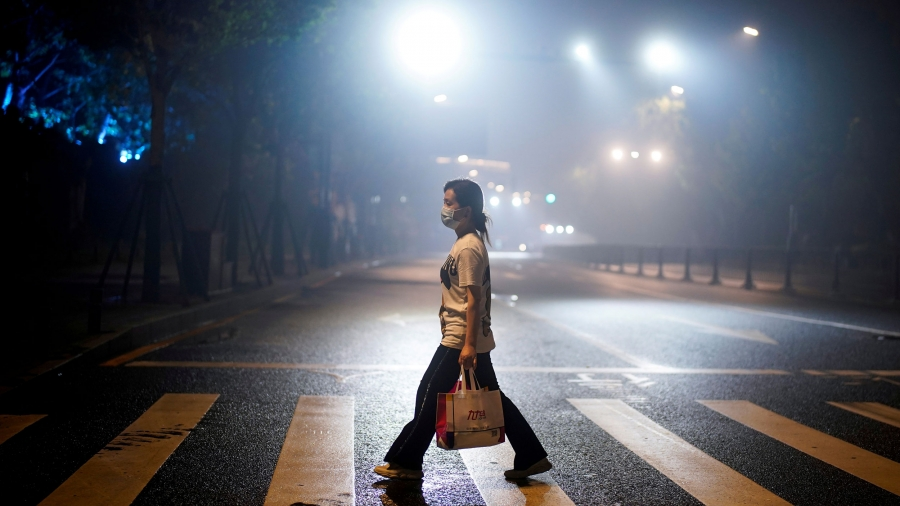 A woman wearing is shown walks on a street in the crosswalk of a street while carrying a bag and wearing a protective face mask with street lights shining above.