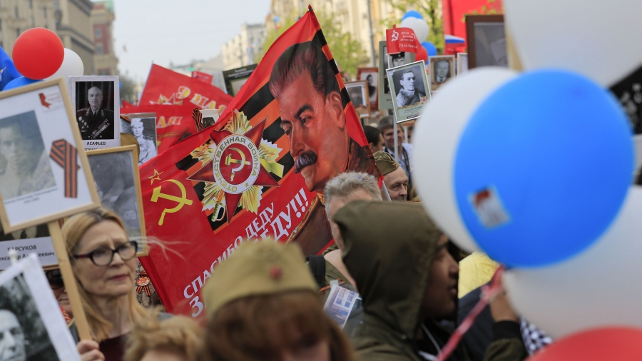 A crowd of people hold balloons, photos and a banner of Joseph Stalin