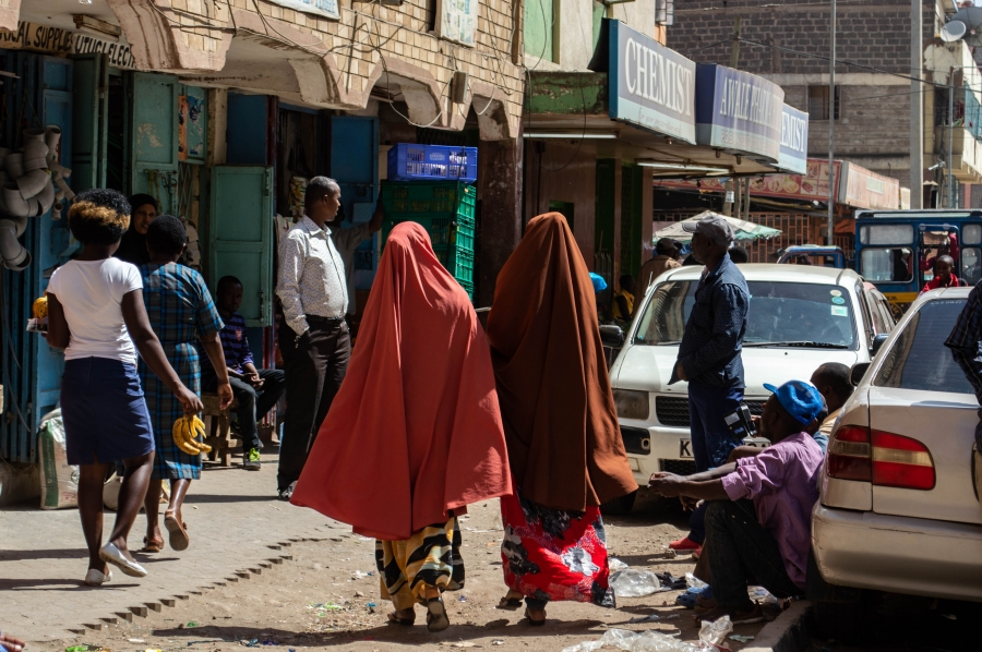 Two women wearing long colorful robes and hijab walk down a street in the Eastleigh area of Nairobi, Kenya.
