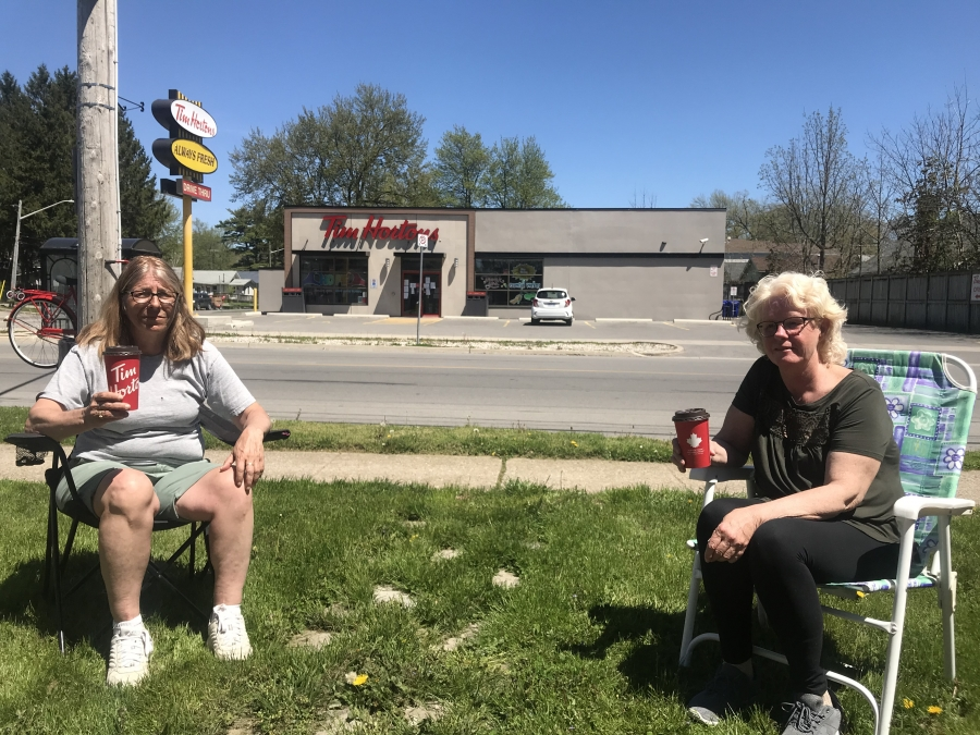 Two women sit in lawn chairs and drink a coffee near a coffee shop.