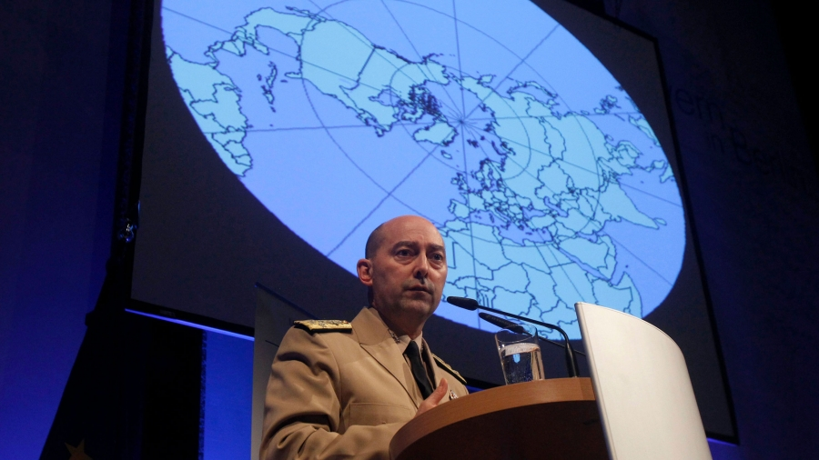 A man stands at a podium with an image of a globe behind him